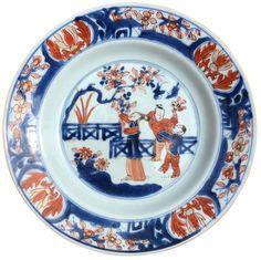 Assiette à décor imari peinte de figures en porcelaine de Chine de la Compagnie des Indes d'époque Kangxi Peinte dans la traditionnelle palette imari, avec au centre cueillant des fruits dans des arbustes dans un jardin clos d'une barrière. Sur l'aile, quatre cartouches sur fond de paysages lacustres.