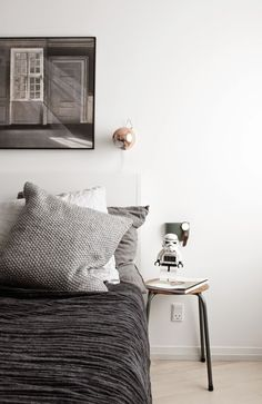 Copper reading light, stool as a bedside table and dark grey bedding in the bedroom of a beautifully captured Danish homePhotography Johanne Dueholm