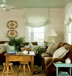 Relaxed Roman shades fit the bill in this casual coastal living room. Striped fabric, hung just below the beaded-board ceiling, elongates the windows, making the walls seem taller.