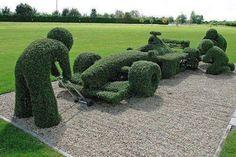 men and race car bush sculptures
