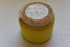 Lemon Yellow Vintage Grosgrain Ribbon 1 3/4″ wide 8 yards long on original paper roll A roll of vintage French grosgrain ribbon in a lemon yellow color. The ribbon is wound in its original packaging. The width on the label is not displayed. The spool reads the following: 10 Me'tres Fixes This rayon material is […]