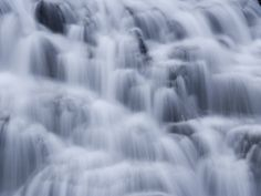 Water rushing in small waterfalls over jagged rocks.