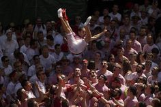 Revelers celebrate during the launch of the 'Chupinazo' rocket, to celebrate the official opening of the 2015 San Fermin fiestas in Pamplona, Spain, Monday, July 6, 2015. Revelers from around the worl