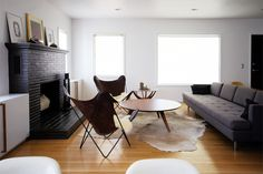 cowhide rug + butterfly chair + painted brick fireplace