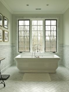 love. Bathroom details- shape of tub, pattern on floor, marble trim on windows, windows.