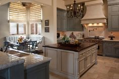 A creamy white island topped with a rich wood countertop centers this stunning Mediterranean kitchen. Soft gray cabinetry is paired with neutral tile flooring, and banquette seating in the corner provides a quaint spot for breakfast.
