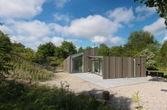 Planks of larch wood pinstripe the exterior of the Dockboot Holiday Home, which huddles at the base of a sand dune on a Dutch island Container Architecture, Timber Cladding, Modern Cottage, Arched Windows, Scandinavian Home, Villa, Exterior, House Styles, Inspiration