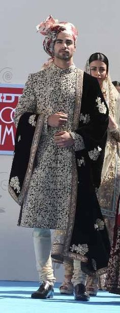 Brilliant Desi Men's Indian Wedding outfit: sherwani IN black and white embroidered fabric, white churidar, colorful floral turban (but the black stole with large embroidered motifs doesn't work). Wedding Dress Men, Indian Wedding Outfits, Wedding Men, Wedding Groom, Wedding Suits, Indian Outfits, Indian Weddings, Farm Wedding, Wedding Couples