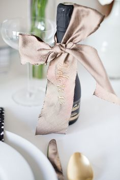 Raw silk ribbon with elegant gold calligraphy turns a mini bottle of bubbly into a beautiful place card.   Photo by Abby Jiu    Calligraphy by Wave Crest Calligraphy   Styling by Healthfully Ever After #FreixenetUSA