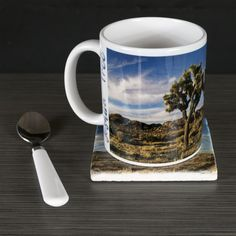 "11oz Mug - Joshua Tree National Park ""Dual-Tree Panorama"". This panorama image of two Joshua Trees was taken in Joshua Tree National Park on lazy summer late afternoon. The image is printed on a 11oz ceramic mug with lettering ""Joshua Tree National Park"" near the handle. This mug is dishwasher safe and will serve both hot and cold drinks. Pictured with both a matching optional glass or Italian marble coaster printed with the same image. Message me for a set of 4 mugs and matching coasters..."