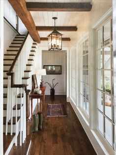 Oh how I love this! Staircase and hallway with gorgeous wood floor, wood beams, and white