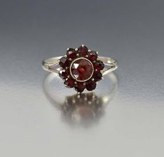From the turn of the last century comes this sweet antique Edwardian Bohemian garnet ring. A large rose cut garnet has a halo of smaller rose cut gemstones depicting a flower. Sterling silver split sh