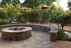 Fire pit with retaining wall that dubs as seating for guests.