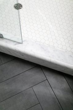 Lauren Evans Interiors designed this guest bath accented by herringbone porcelain tile floors, Visual Comfort door knocker sconces, Carrera marble shower surround and white pebble shower pan tile. Shower Floor Tile, Bathroom Floor Tiles, Modern Bathroom, Black Bathroom Floor, Black And White Master Bathroom, Marble Tile Bathroom, Tile Grout, Black Floor, Bathroom Cabinets