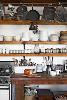 Exposed Shelving:  Rustic wood looks even more lovely against crisp white walls and dishes. The owner of this northern California home used Douglas fir for the shelving and redwood for the farm table. Exposed shelving and hanging pots are classic features of a country kitchen.