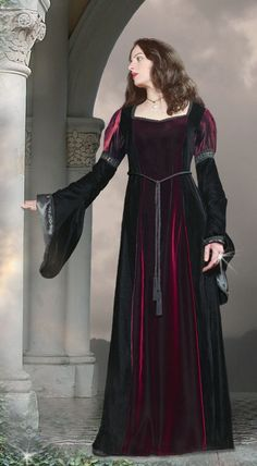 Classic Medieval style gown. In black Panne velvet with a contrasting purple or wine front panel and sleeve head in shot silky velvet. The elaborate drop sleeves are fully lined in black satin. The sleeves and neck line are trimmed with an ornate black braid, this is complemented by