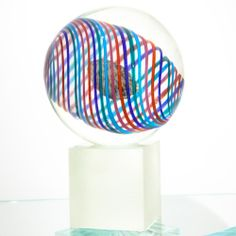 The Colourful Sphere is a sculpture made up of 3 different parts, processed separately: the base is in bevelled glass, the sphere is in Murano crystal glass with inclusion of multicoloured spiral cannas, whereas the core is in vitreous paste and coloured grains.