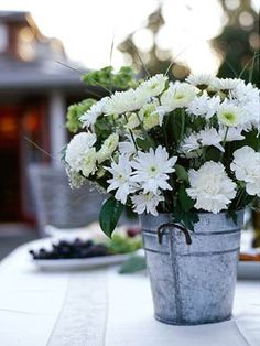 Tin Bucket - Casual settings often play host to informal afternoon weddings. This centerpiece adds a bit of country flair with a tin container and arrangement of white mums, carnations, and daisies -- an budget-friendly, yet festive, way to celebrate Country Wedding Centerpieces, Wedding Decorations, Wedding Centrepieces, Bucket Centerpiece, Centerpiece Ideas, Simple Centerpieces, Daisy Centerpieces, Quinceanera Centerpieces, Centerpiece Flowers
