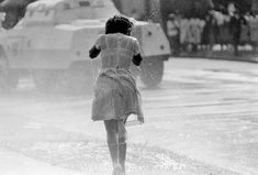 Young black woman, soaked by a fireman's hose as an anti-segregation march is broken up by police, in Birmingham, Alabama, on May 8, 1963. In the background is a police riot wagon. (Photo by AP Photo)