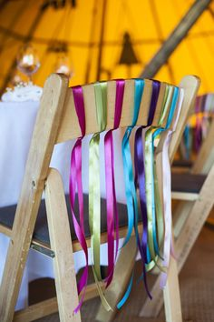 Bright coloured ribbon streamers on the back of the chairs | Bright Colour Scheme | Outdoor Tipi Reception | Coastal Welsh Wedding | Image by Eleanor Jane Photography | http://www.rockmywedding.co.uk/kirsty-adrian/