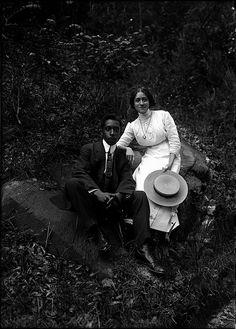 Portrait of a couple seated on rocks in an outdoor setting; woman holding a straw hat. [ca. 1910-1920]
