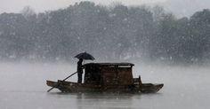 20151207 - Homem usa guarda-chuva para se proteger da neve ao atravessar um lago em Zhejiang, China. PICTURE: Reuters
