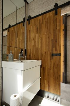 Sliding bathroom door - apparently made with custom countertops from Ikea! Great idea to bring in an industrial feel for the bathroom, and to open up the space