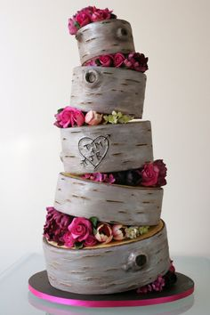 Topsy turvy rustic wedding cake with log slices complete with carved initials