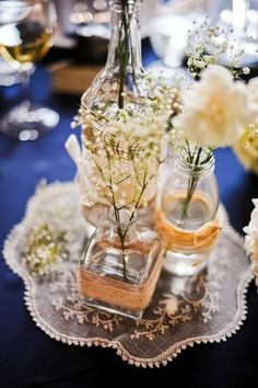 Various bottles (maybe from MB or NJ collections for different sizes rather than all mason jar height), burlap, and flowers as table centerpience