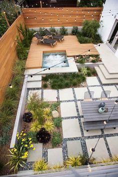 jardin design contemporain aménagé avec un jacuzzi, un salon de jardin en bois et décoré de graviers et de guirlandes lumineuses