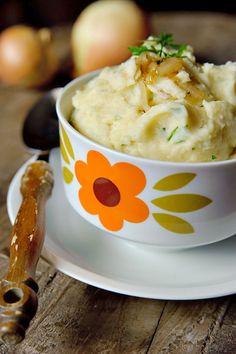 Bereiden:  Kook de aardappelen in ruim gezouten water in ca. 20 minuten goed gaar.  Verhit de boter en voeg de uien toe. Bestrooi ze met wat zout en peper en temper het vuur. Laat de uien in ca. 20 tot 30 minuten zacht, zoet en bruin bakken. Blijf roeren en voeg boter toe als de uien te droog worden.  Giet de aardappelen af en laat ze even droog stomen. Terwijl de aardappelen droog stomen doe je de helft van de uien samen met de warme melk in een blender en pureer dit.
