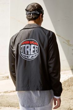 """From our exclusive Forever 21 x Vision Street Wear™ collection, this coach jacket features a basic collar, long sleeves with elasticized cuffs, a buttoned front,  two slip pockets, a """"Vision"""" graphic logo on the front, and a variety of embroidered logo patches on the front and back."""