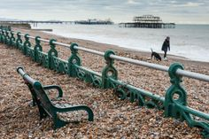 The promenade on Brighton beach is covered with pebbles as the high tide and storm subsided