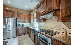 Brown cabinetry with stainless appliances- love this look