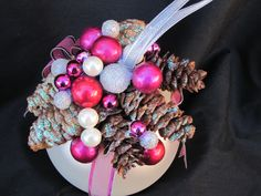 Cream colored ornament decorated with pinecones and berries