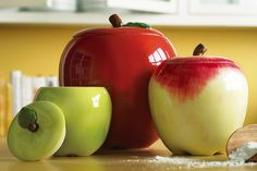 """Apple Decor Kitchen Canisters: An apple a day helps keep kitchen staples handy and livens up your kitchen with orchard bright freshness and color. Delightful set of 3 hand-painted and glossy-glazed ceramic canisters has tops fitted with sure-fit silicone seals to maintain the freshness of coffee, sugar, flour, tea and more. Large: 7""""H holds 50 oz., Med.: 5 1/4""""H holds 18 oz., Small: 4 1/4""""H holds 10 oz.    Condition: New..."""