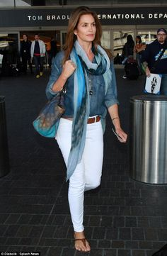 Cool beauty: Cindy Crawford showed her stylish edge in white skinny jeans and scarf as she...