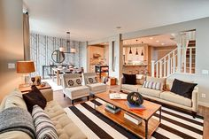 Great room furniture layout.  I love the wallpaper in the dining room and the striped rug.
