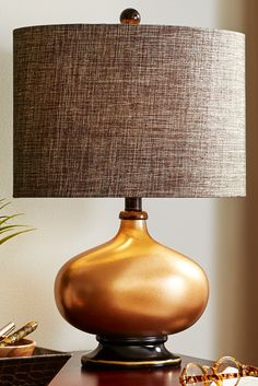 From its broad, turned base to its rounded finial on top, Pier 1's beautiful Gilded Copper Base Table Lamp creates a stable, horizontal volume not often seen. The copper-colored finish contrasts nicely with a linen/poly drum shade that creates an effect at once modern and classic.