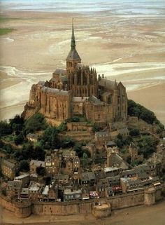 Mont St. Michel, France.  There as a child and remember it vividly - holes in the wall for men with bows and arrows to defend it!  Cool!