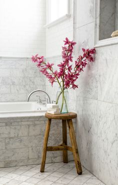 the timber stool adds warmth and charm to the tiled bathroom.  Image - Perth Soap Company