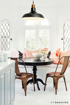 Dining nook with a black round table, rust chairs, a black pendant light, and blush pillows