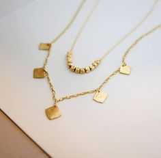 A chic set of 2 gold filled dainty necklaces. A simple and minimalist layered necklace set. This set consists of nuggets necklace and a 5 square discs necklace. The nuggets necklace is a bit shorter than the other necklace. Both necklaces are made from high-quality 14K gold filled. Unlike Gold Plating the gold in gold filled jewelry is mechanically bonded to the base metal, and it will not wear off or turn black. Each necklace is gorgeous worn on its own, but since they complement each…