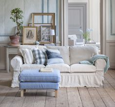 Cozy Country. Ektorp 3 seater sofa cover in Loose Fit Country style in Unbleached Linen. Karlstad foostool cover in Vreta Gingham Check Blue/White. Cushion covers in Stockholm Stripe Sand Beige, Cloud Brera Quadretto by Designers Guild and Silver Grey Vallsta from our Artist Series. www.bemz.com
