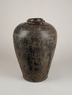 Wine jar, 12th-13th century | Jars like this were used in Laos at festivals or celebratory events, such as the rice festival. Celebrants sat around the jar drinking a sweet, spicy rice wine (ruon) through curved reeds (can). The jar is typical of a type of large ceramic wine or storage vessel produced in the so-called Angkorean region of Southeast Asia, which at its zenith extended from Cambodia to southern Laos and across to northeastern Thailand.