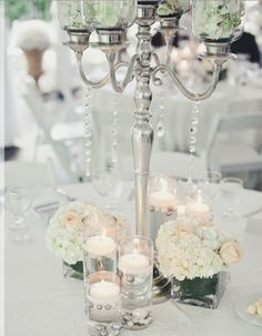 The base of the candelabras will be surrounded by silver mint julep cups filled with white roses, tall votives with floating candles in pink water and gold mercury glass votives.