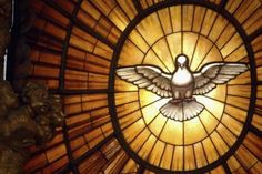 The Novena to the Holy Ghost: A stained-glass window of the Holy Spirit overlooking the high altar of Saint Peter's Basilica.