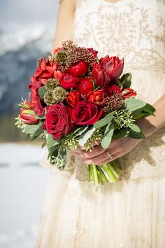 Red bridal bouquet with roses, ranunculus, scabiosa pods, tulips, trachelium and seeded eucalyptus. Designed by Forget-Me-Not Flowers,Banff. Photo by Kim Payant Photography.http://www.kimpayantphotography.com/
