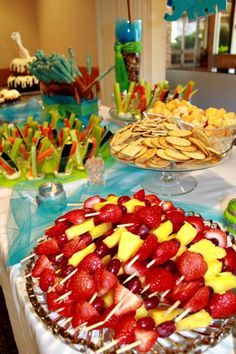 No-nonsense but nice food spread for baby shower or party. Veggie sticks in cup with dressing in the bottom. Fruit kabob of strawberries, grapes, & pineapple. Pretzel rods. Cheese and crackers. Easy to make and serve Bundt cake. Bottles of water with especially printed labels.