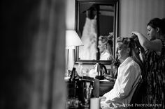 Sarah prepares for the wedding day ahead with her gorgeous Ian Stewart wedding gownhanging on the bed in the reflection of the mirror.